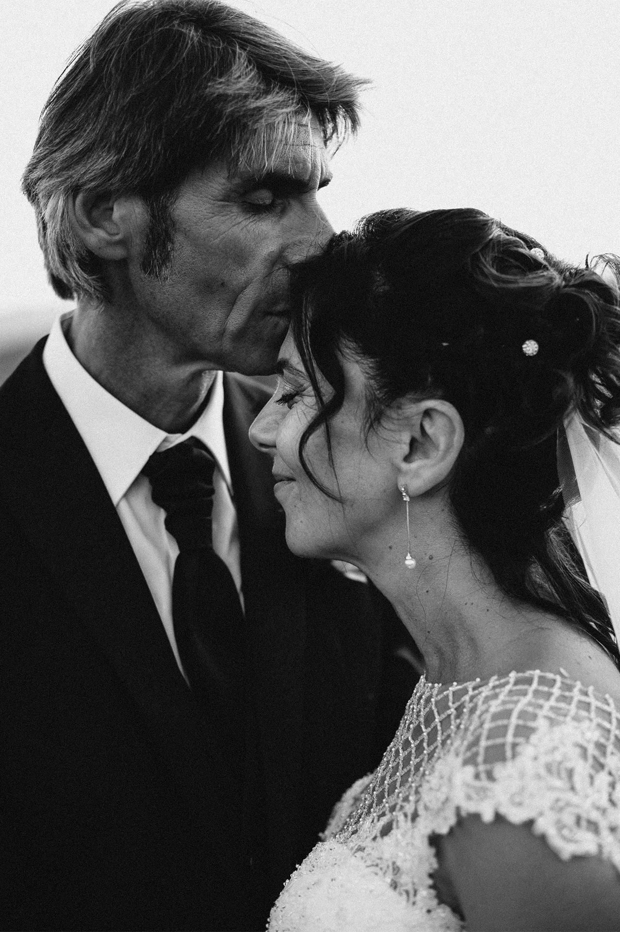 sposo bacia sulla fronte la sposa