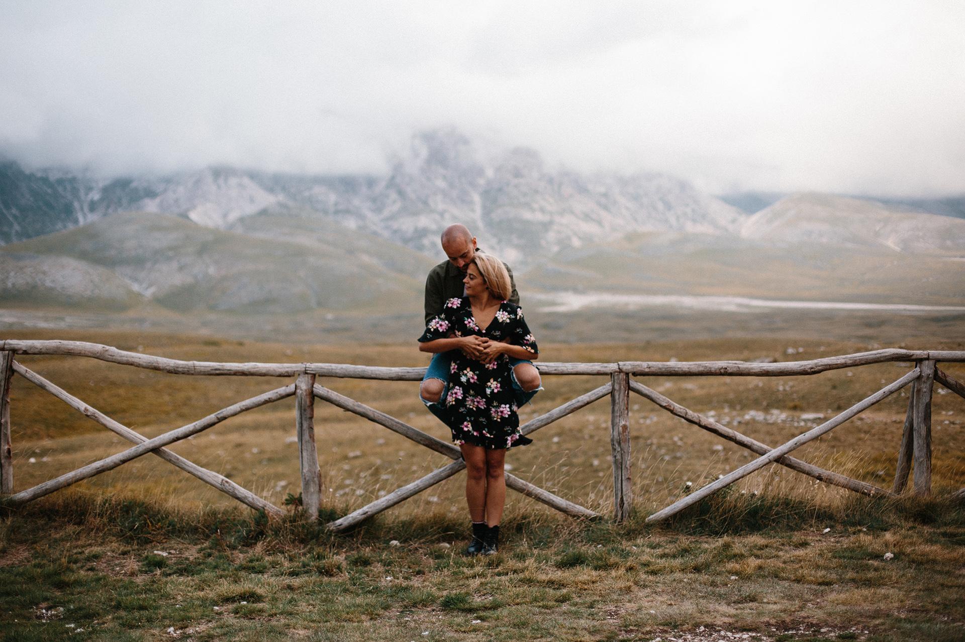 coppia seduta su una staccionata in montagna