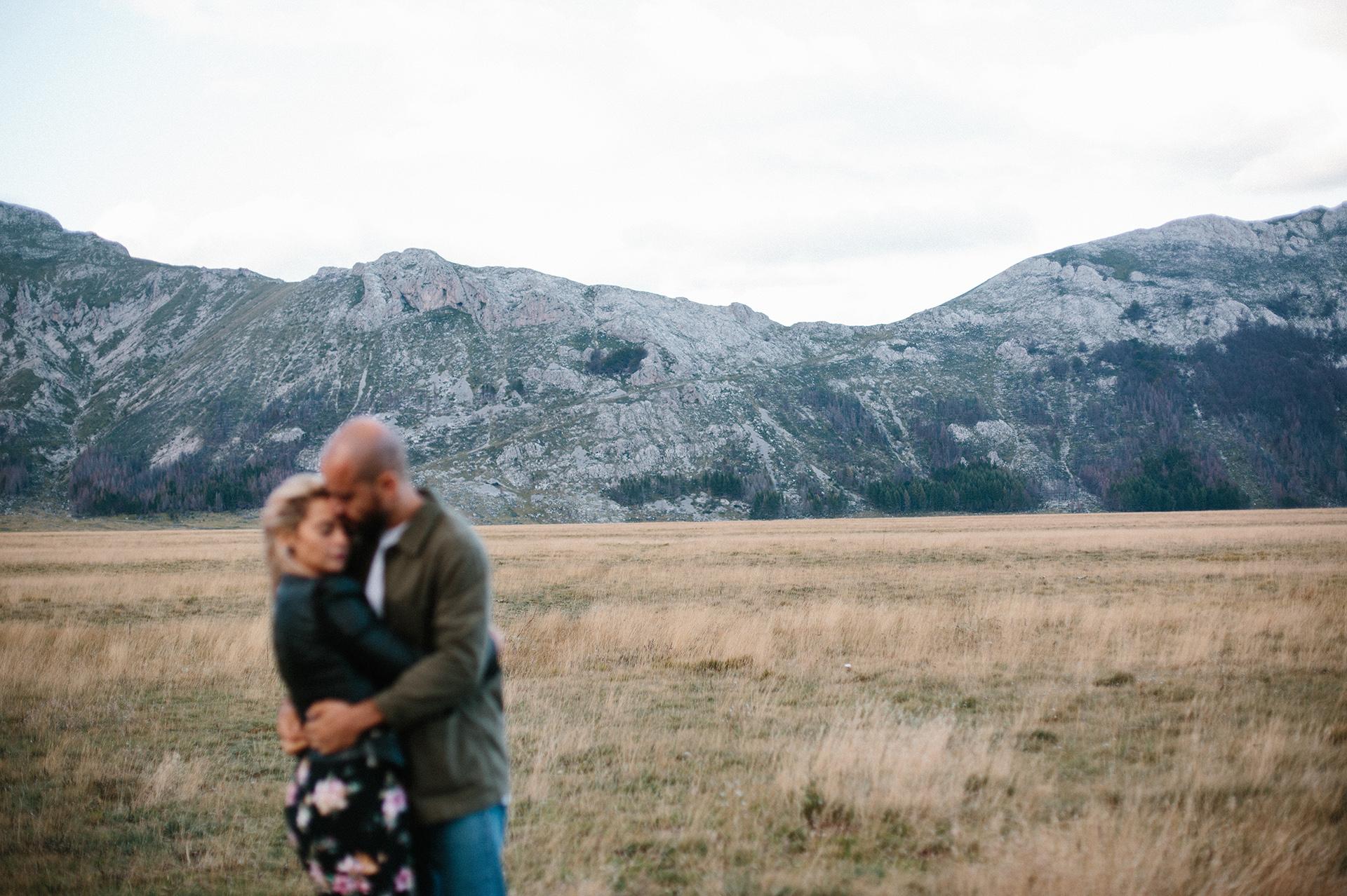 Coppia che si abbraccia e alle spalle la montagna