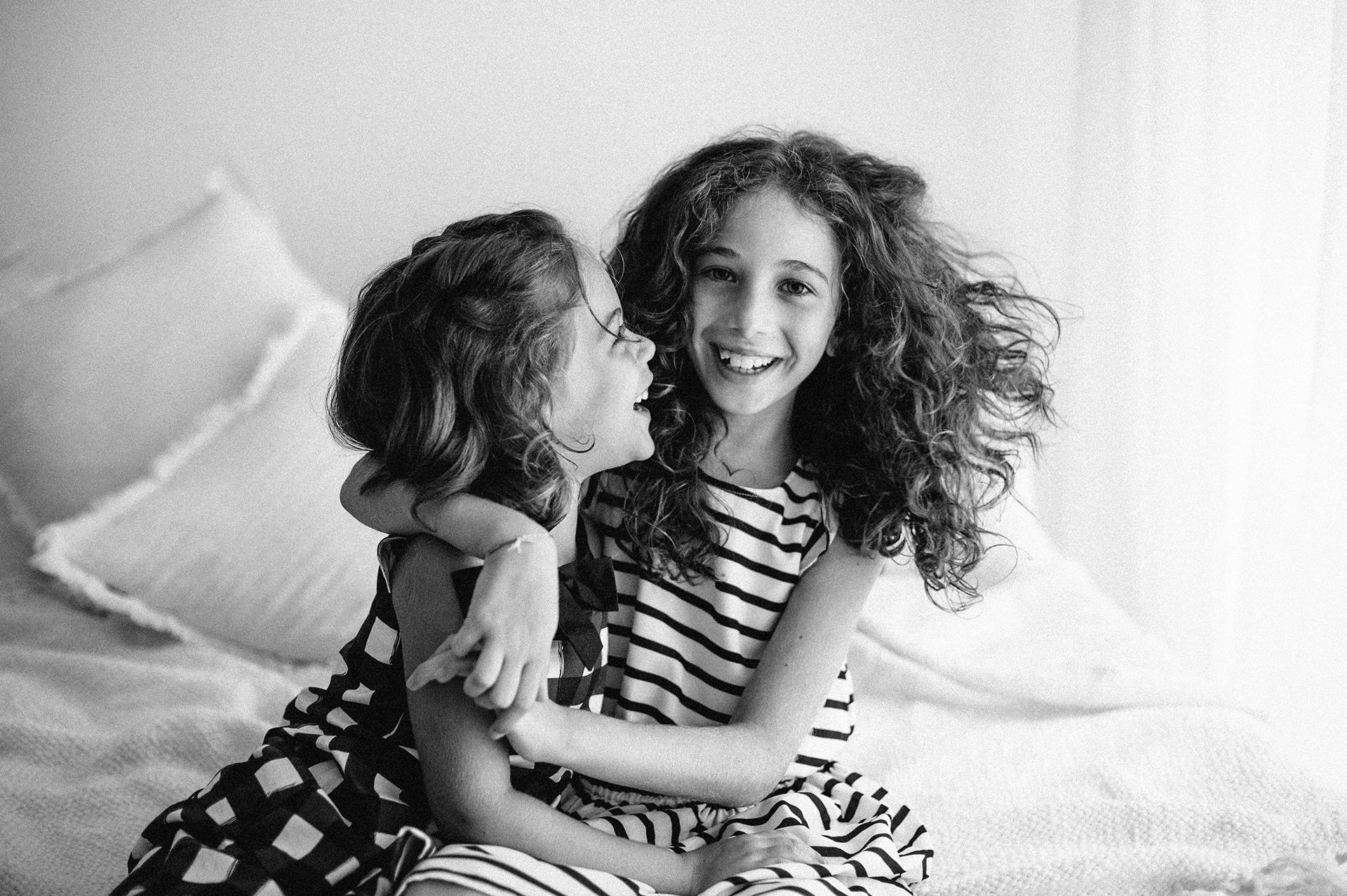 due sorelle si abbracciano ridendo