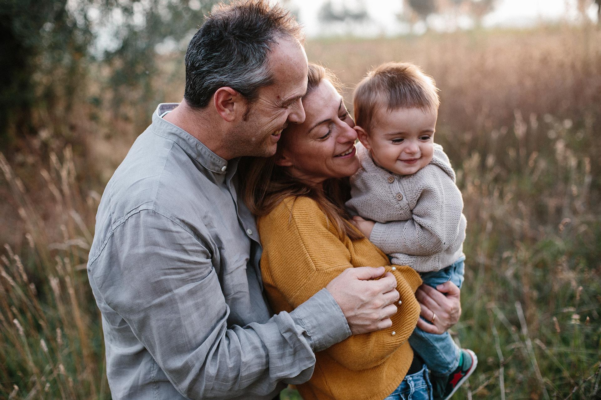 famiglia si abbraccia tra l'erba alta