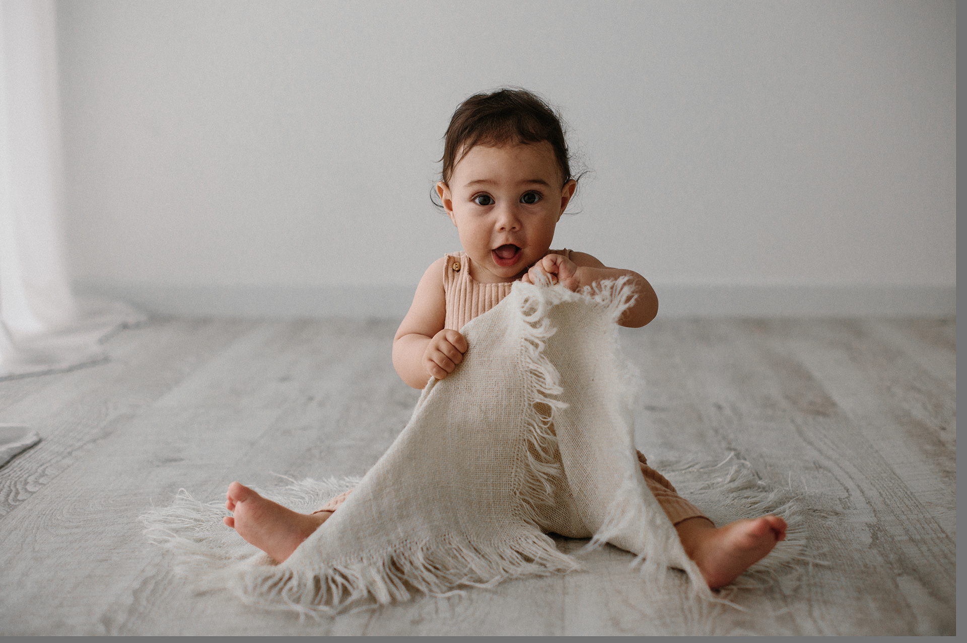 bebè si nasconde dietro una coperta