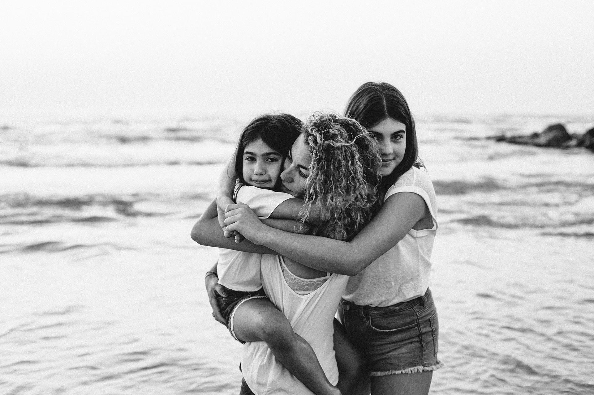 bambine abbracciano la mamma al mare