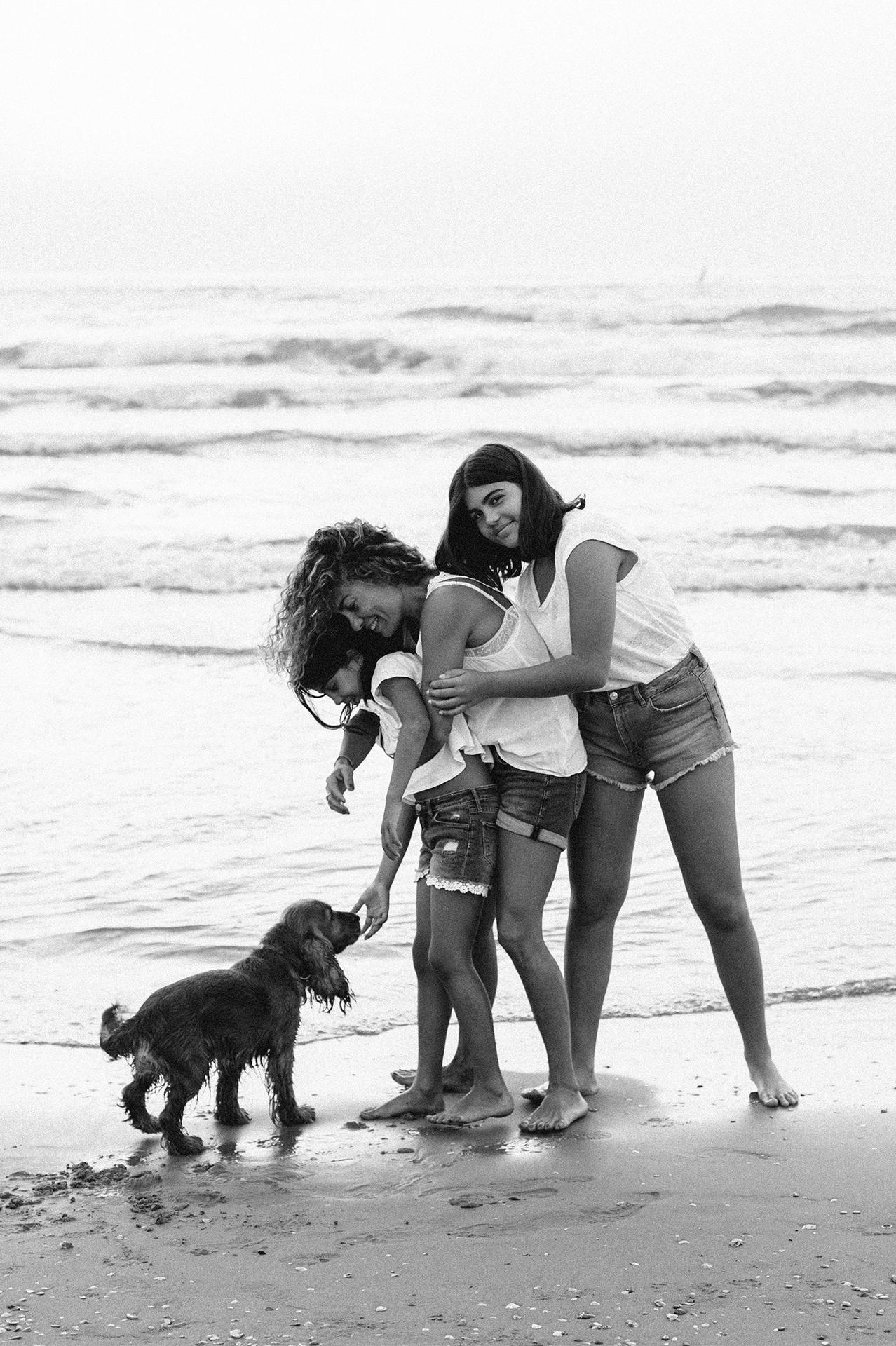 famiglia che gioca con il cane in spiaggia