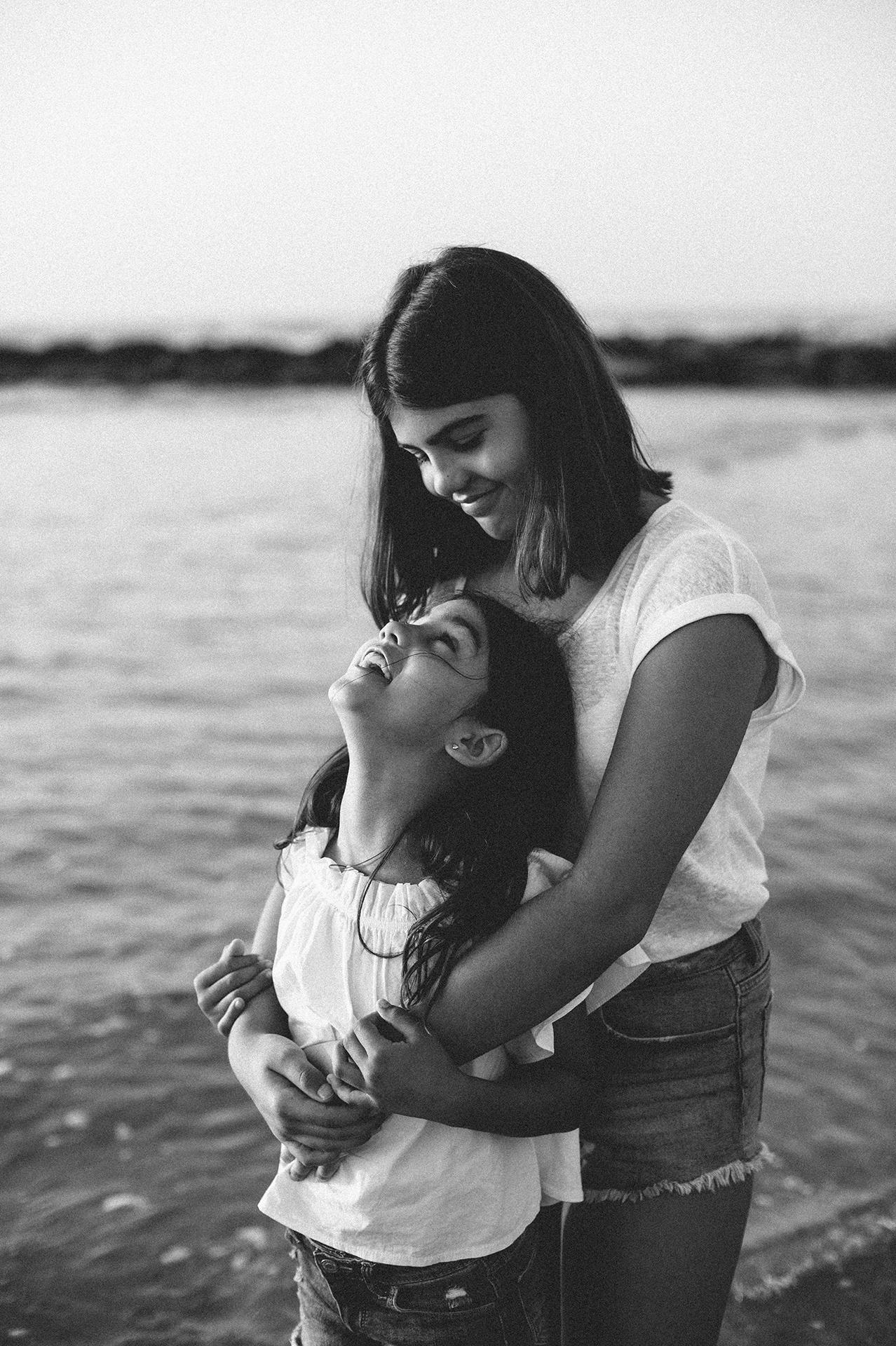 sorelle si abbracciano al mare