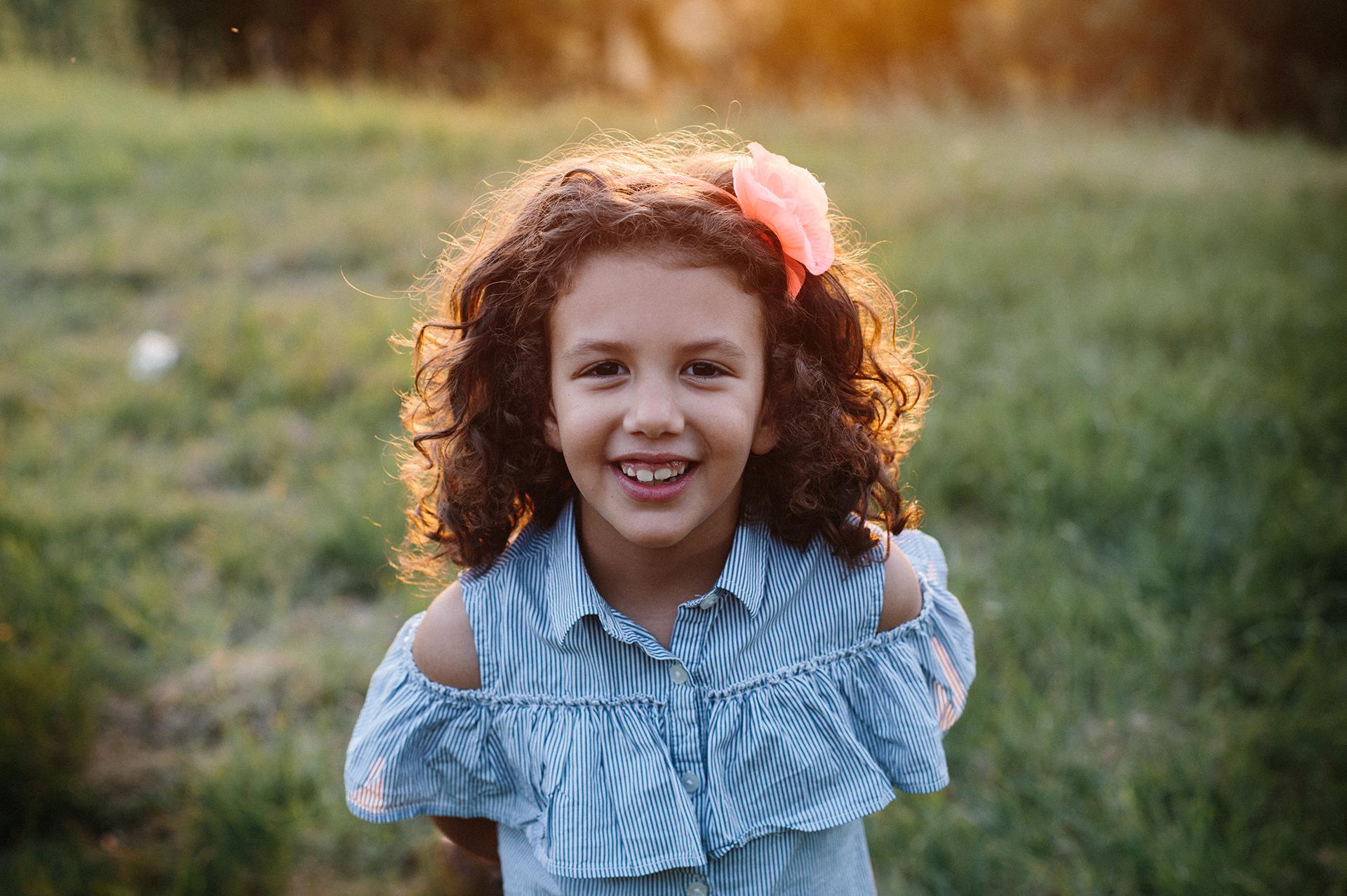 bambina sorride nel prato al tramonto
