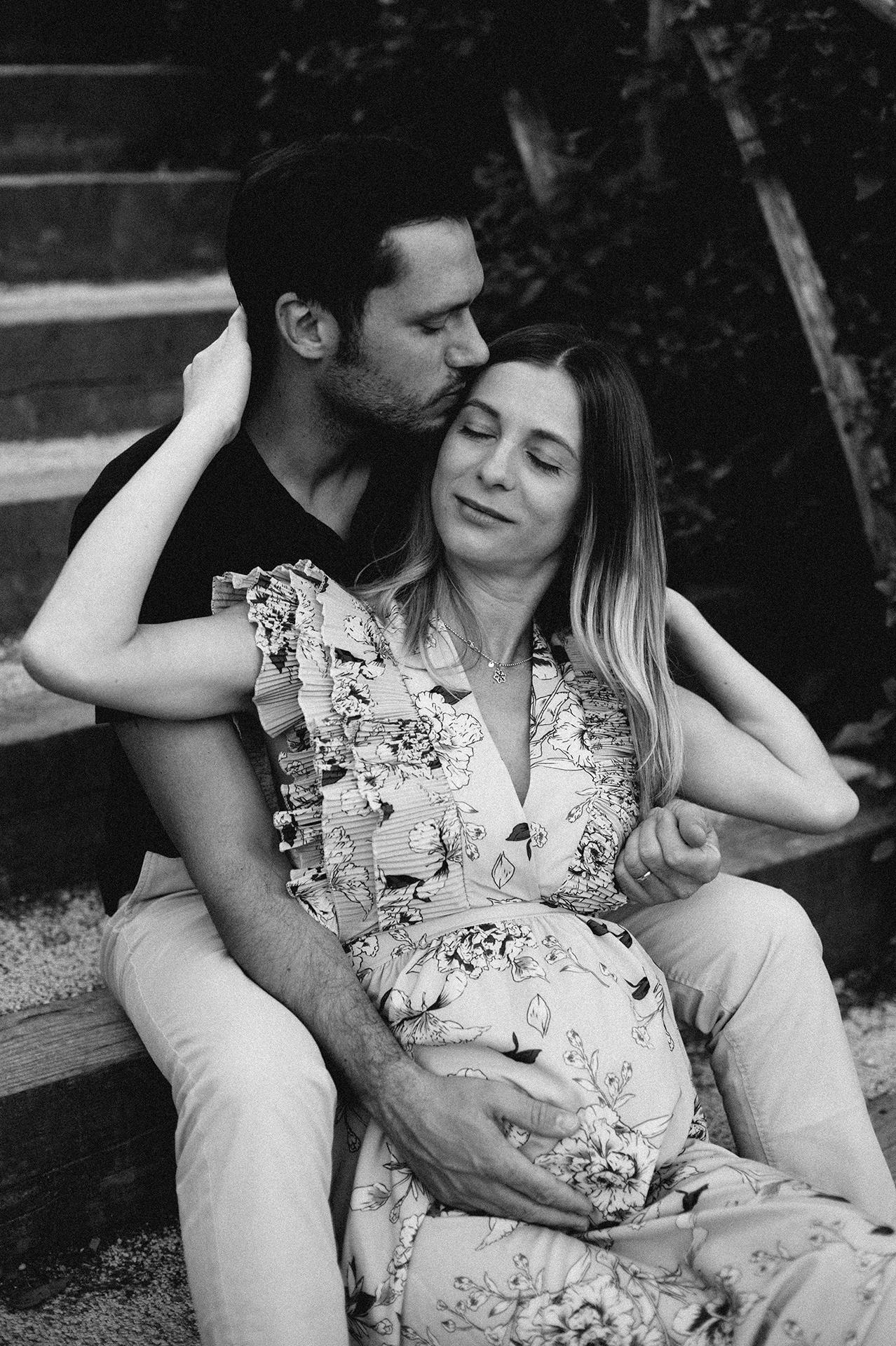 coppia in dolce attesa seduti sui gradini mentre si abbracciano