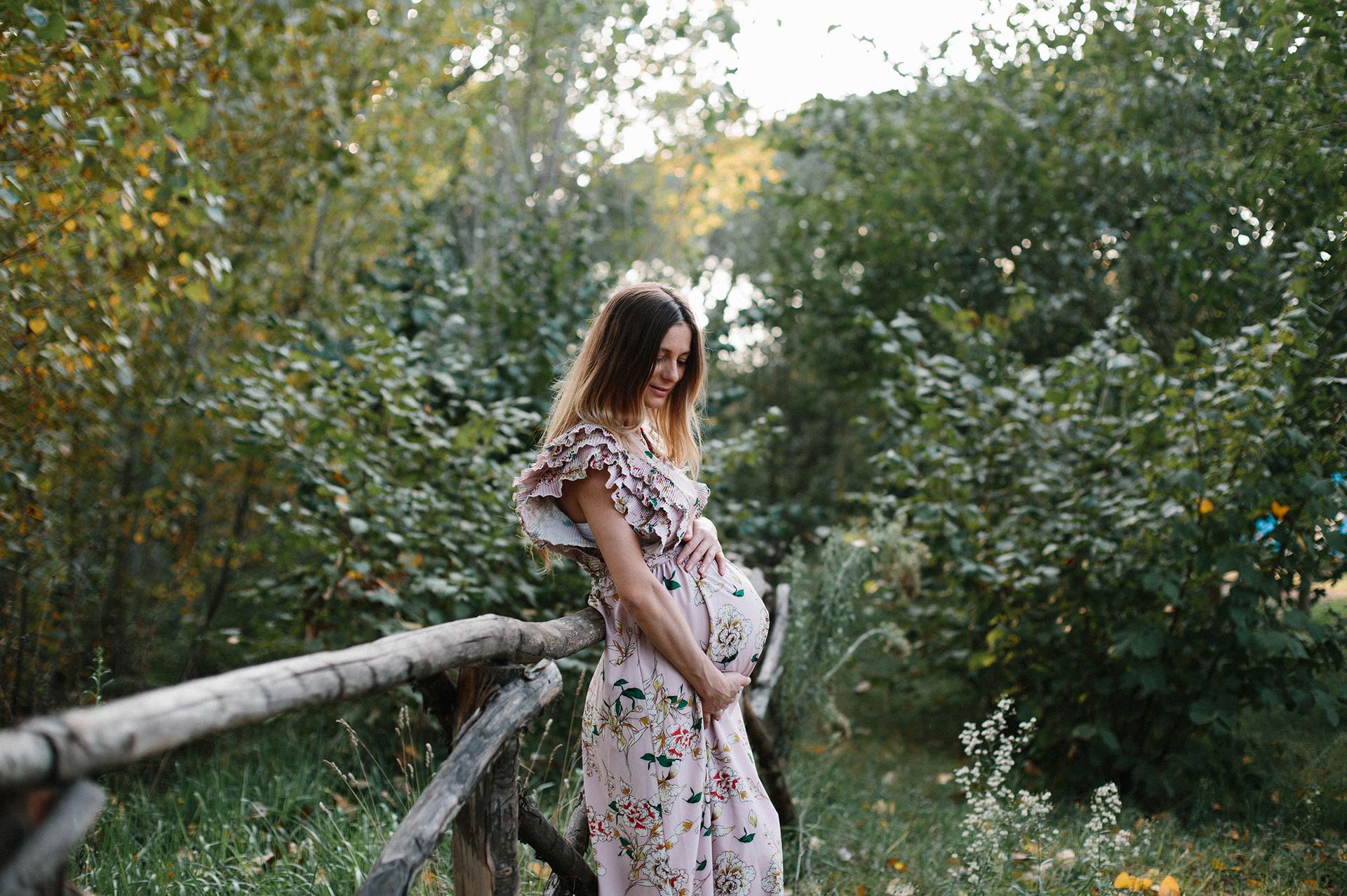 donna con pancione appoggiata ad una staccionata