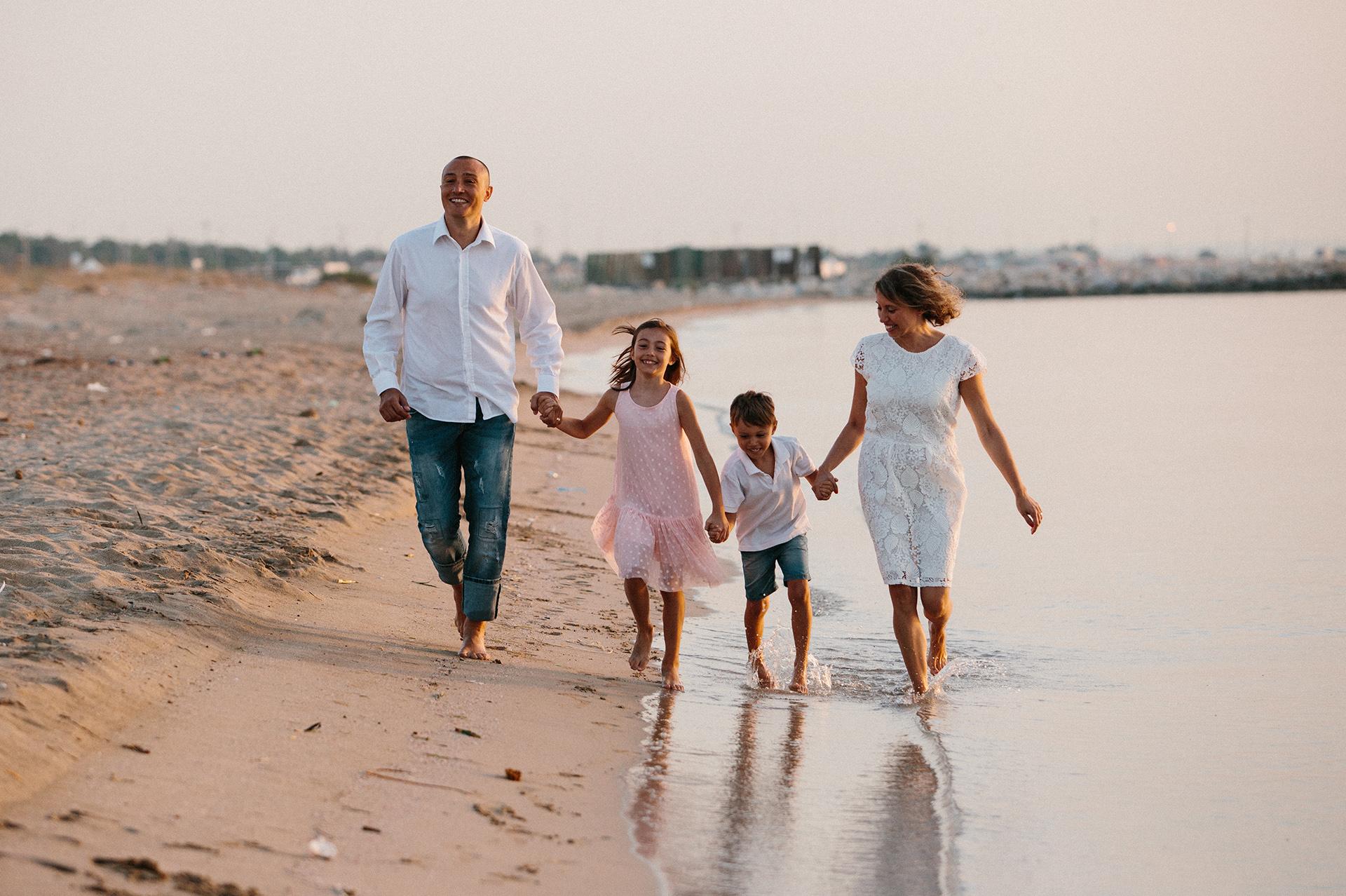 famiglia con due bambini cammina in riva al mare