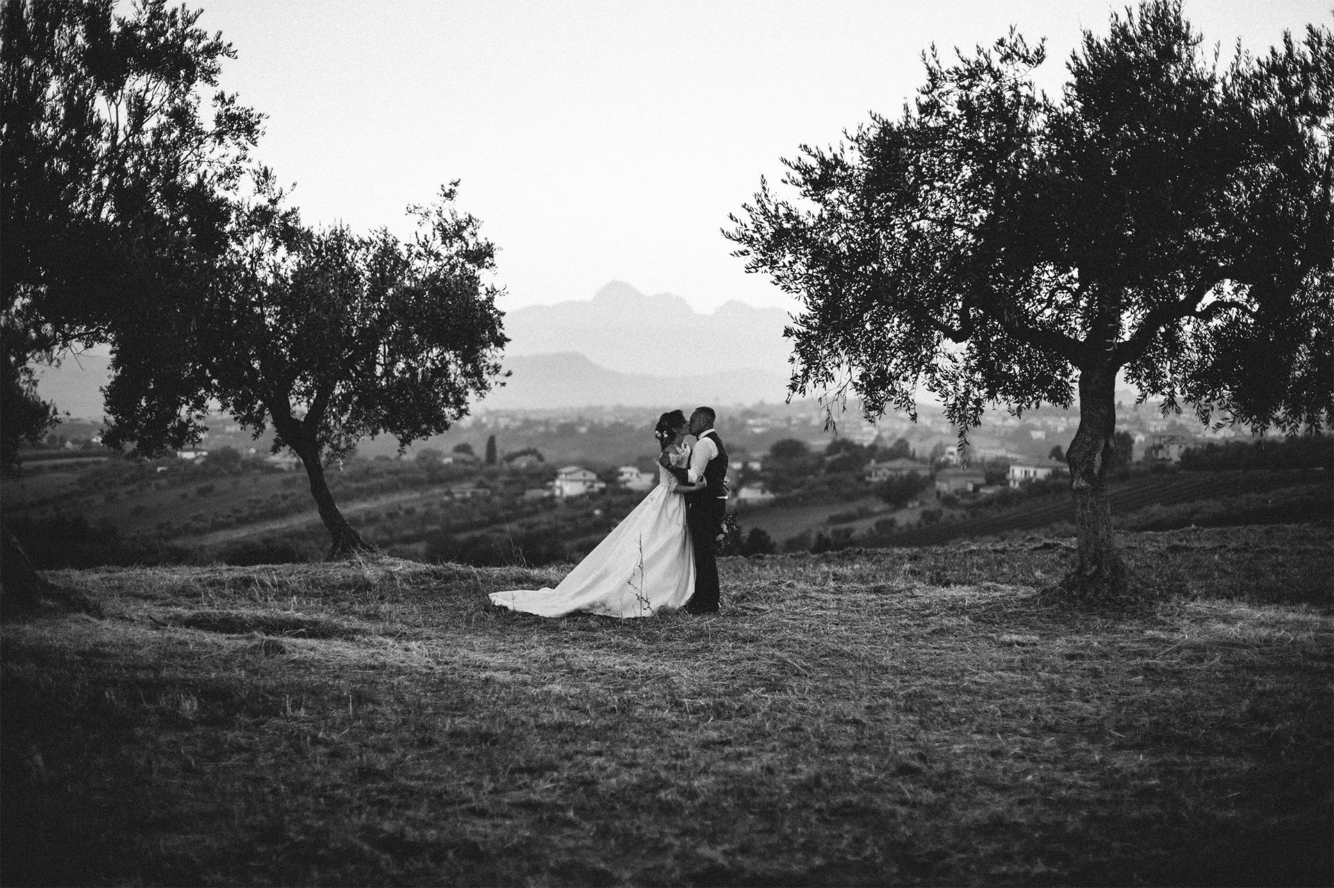 sposi si baciano davanti alle montagne