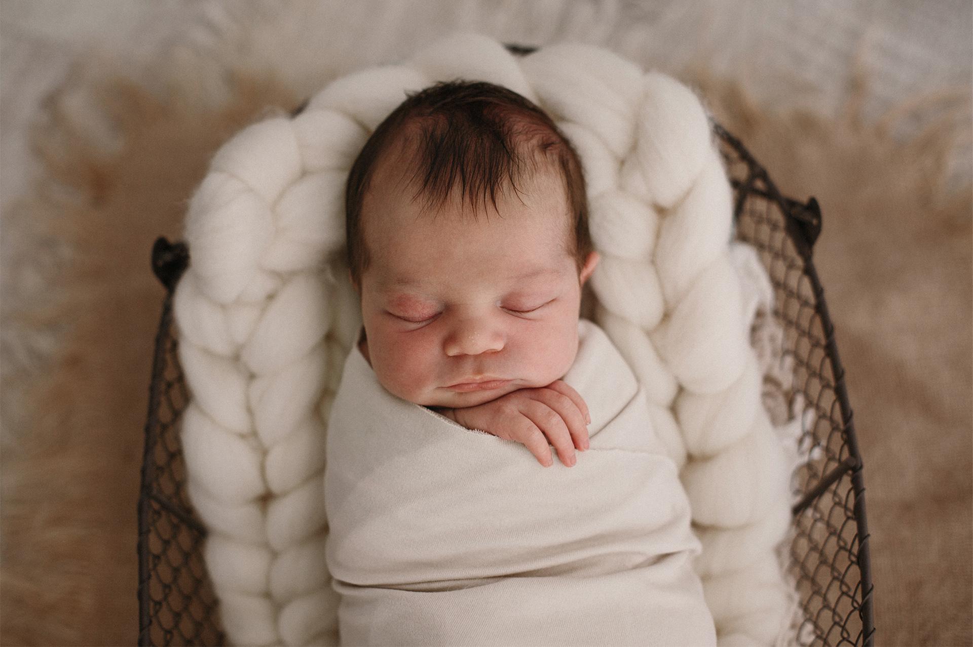neonato dorme fasciato di bianco