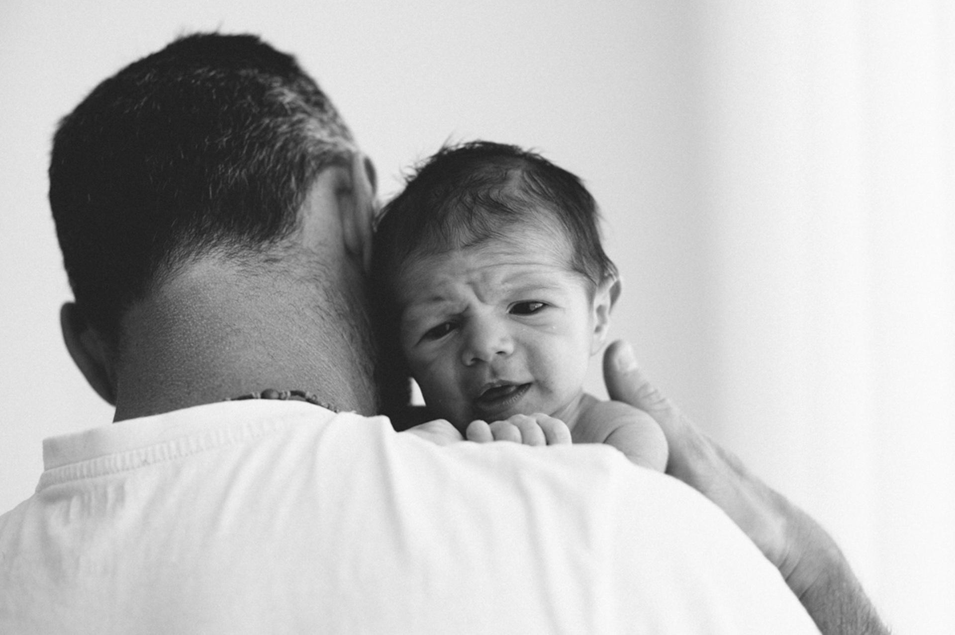 neonato appoggiato alla spalla del papà