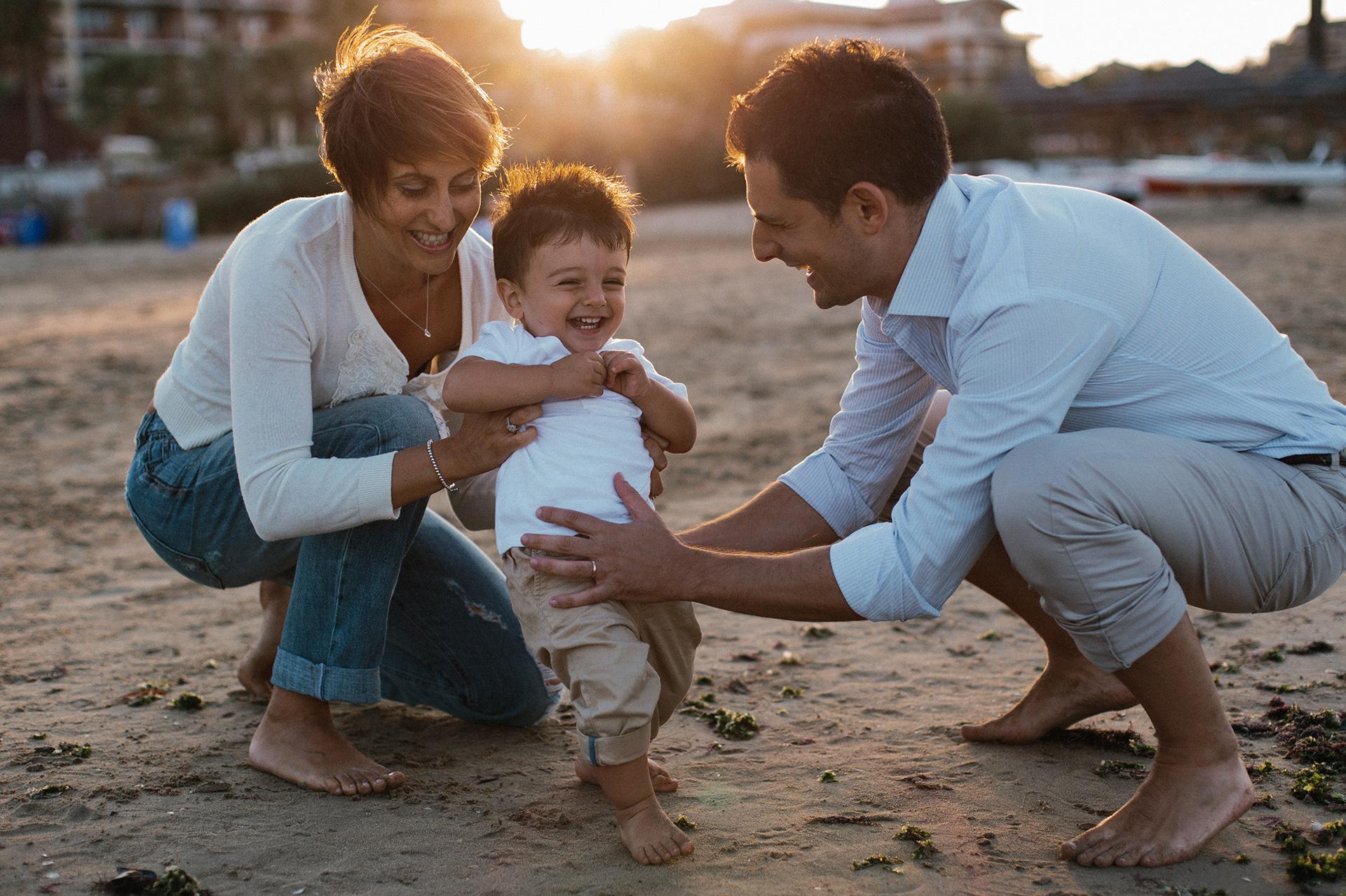 mamma e papà giocano con il bambino in spiaggia