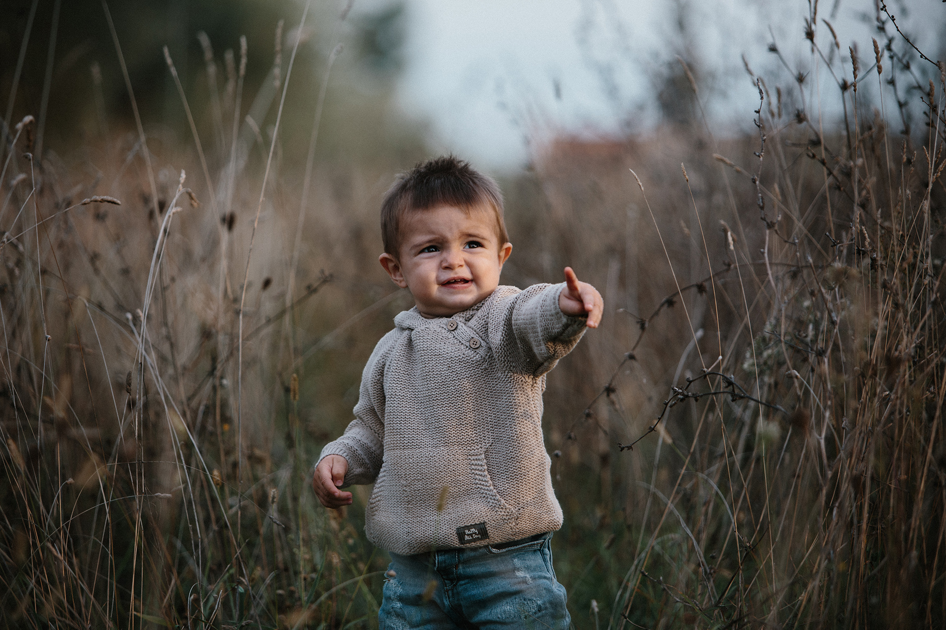 bambino con maglione tra l'erba alta
