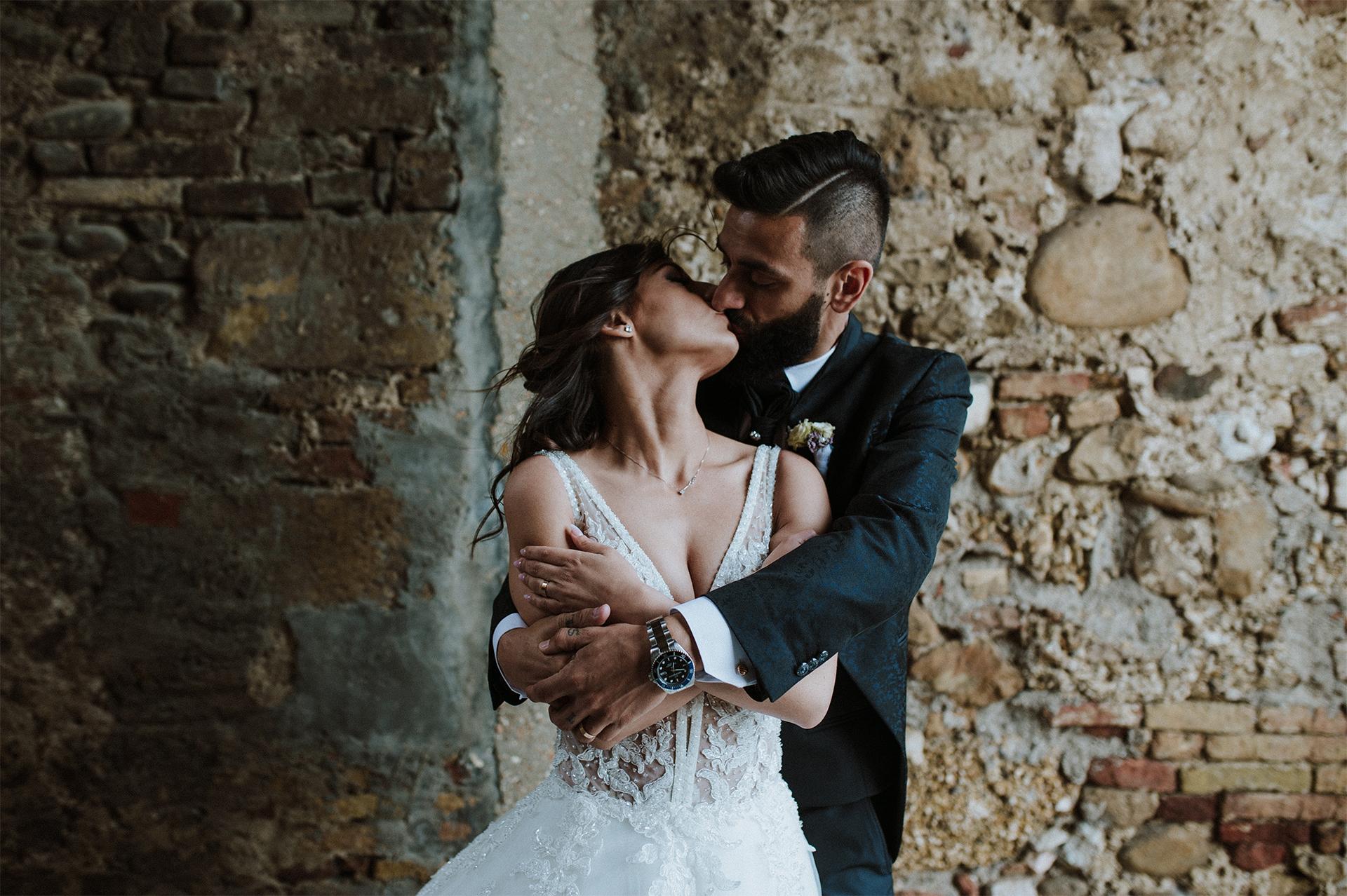 sposi si baciano appoggiati al muro